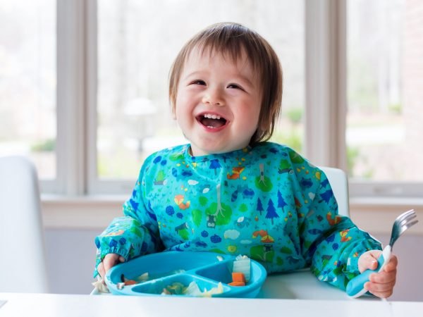 Happy toddler boy with a big smile eating food