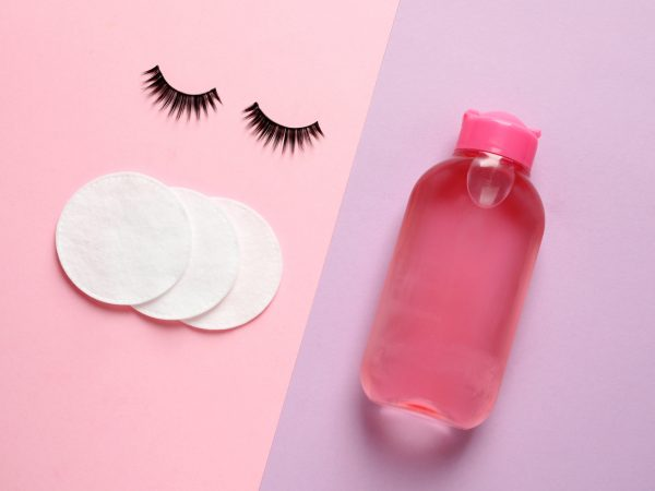 False eyelashes, cotton pads and makeup remover on color background, flat lay