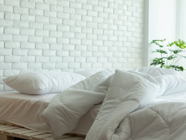 Messed bed with white pillow and blanket with natural light in bedroom in the morning,Messy bed after wake up,Messy bed and Cozy Bedroom Concept