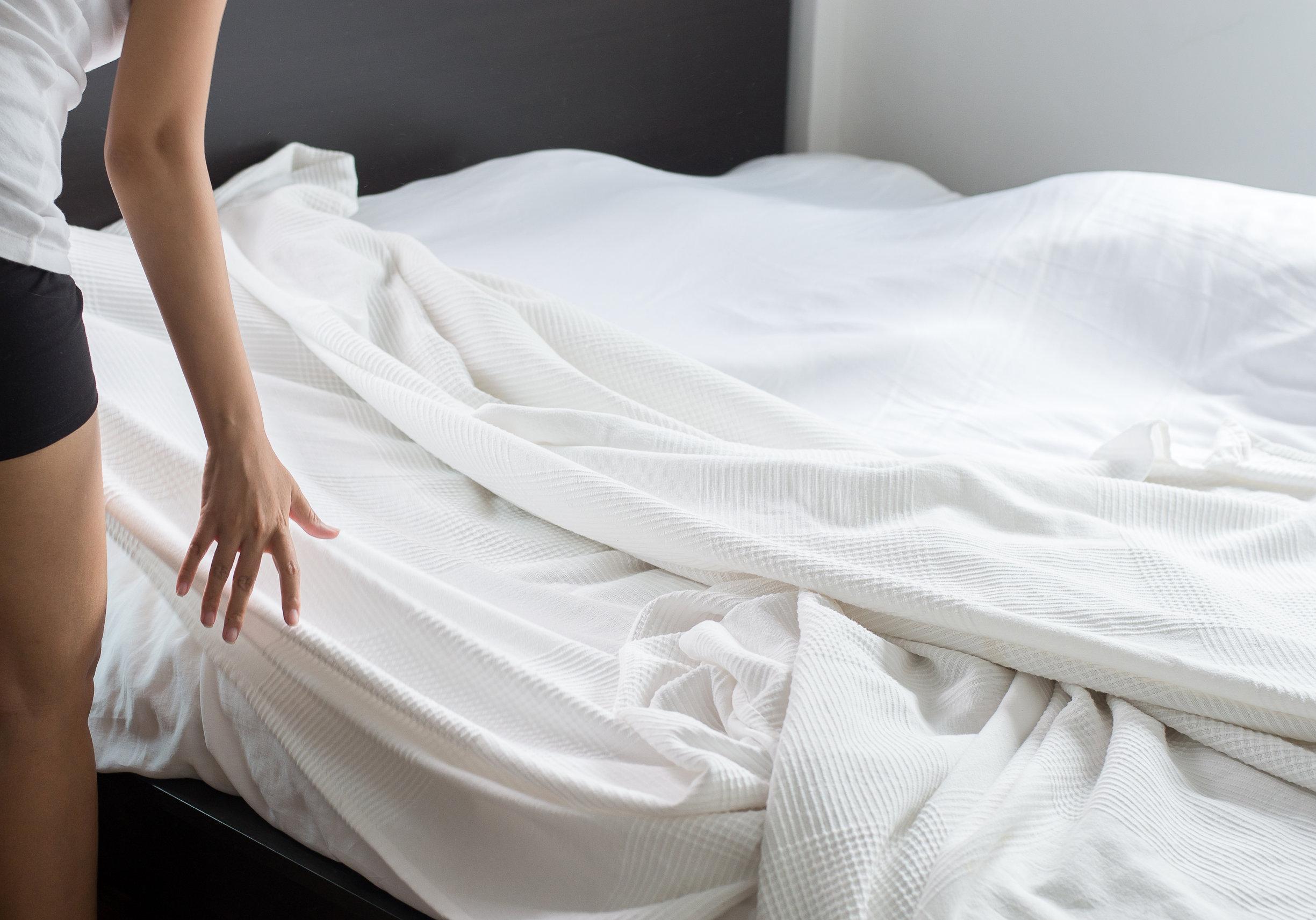 Mujer haciendo su cama en la habitación después de despertarse
