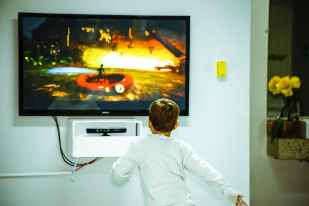 Niño viendo TV en soporte de pared