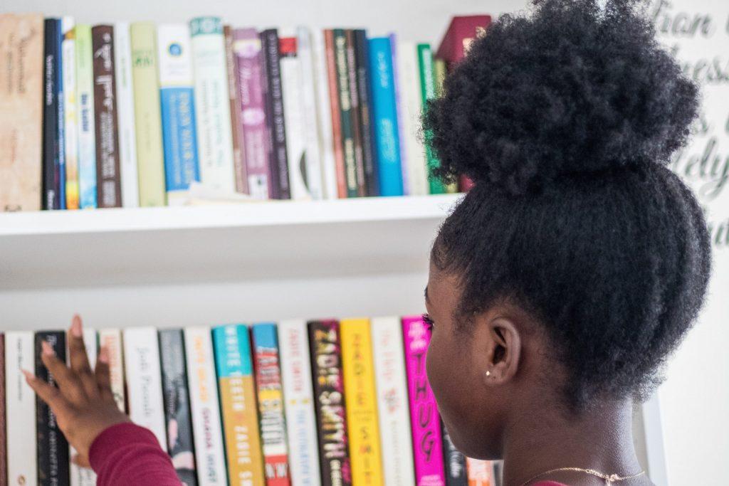 Niña con rizos eligiendo libros de una estantería