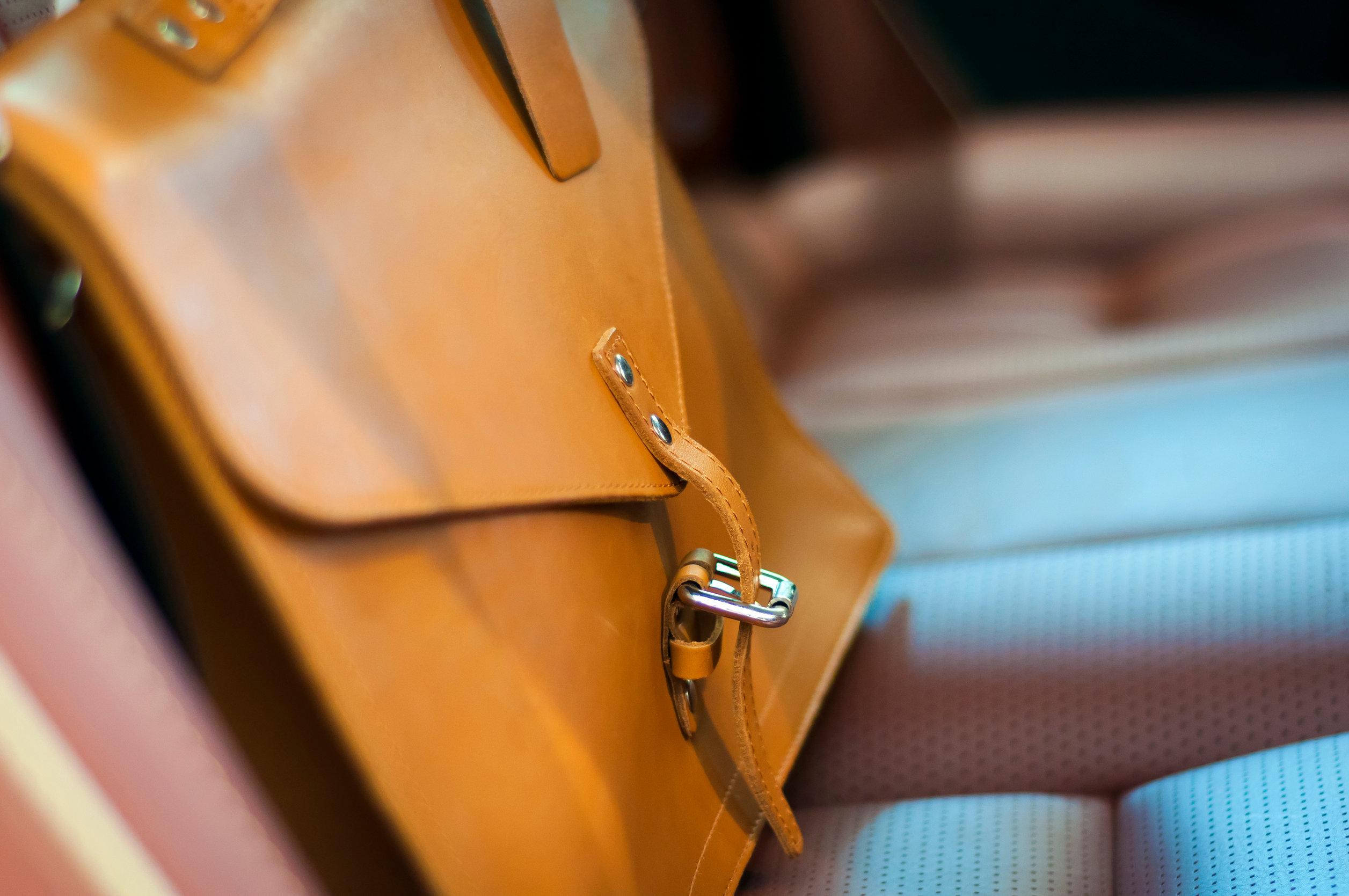 maletín de cuero marrón en el asiento trasero del coche