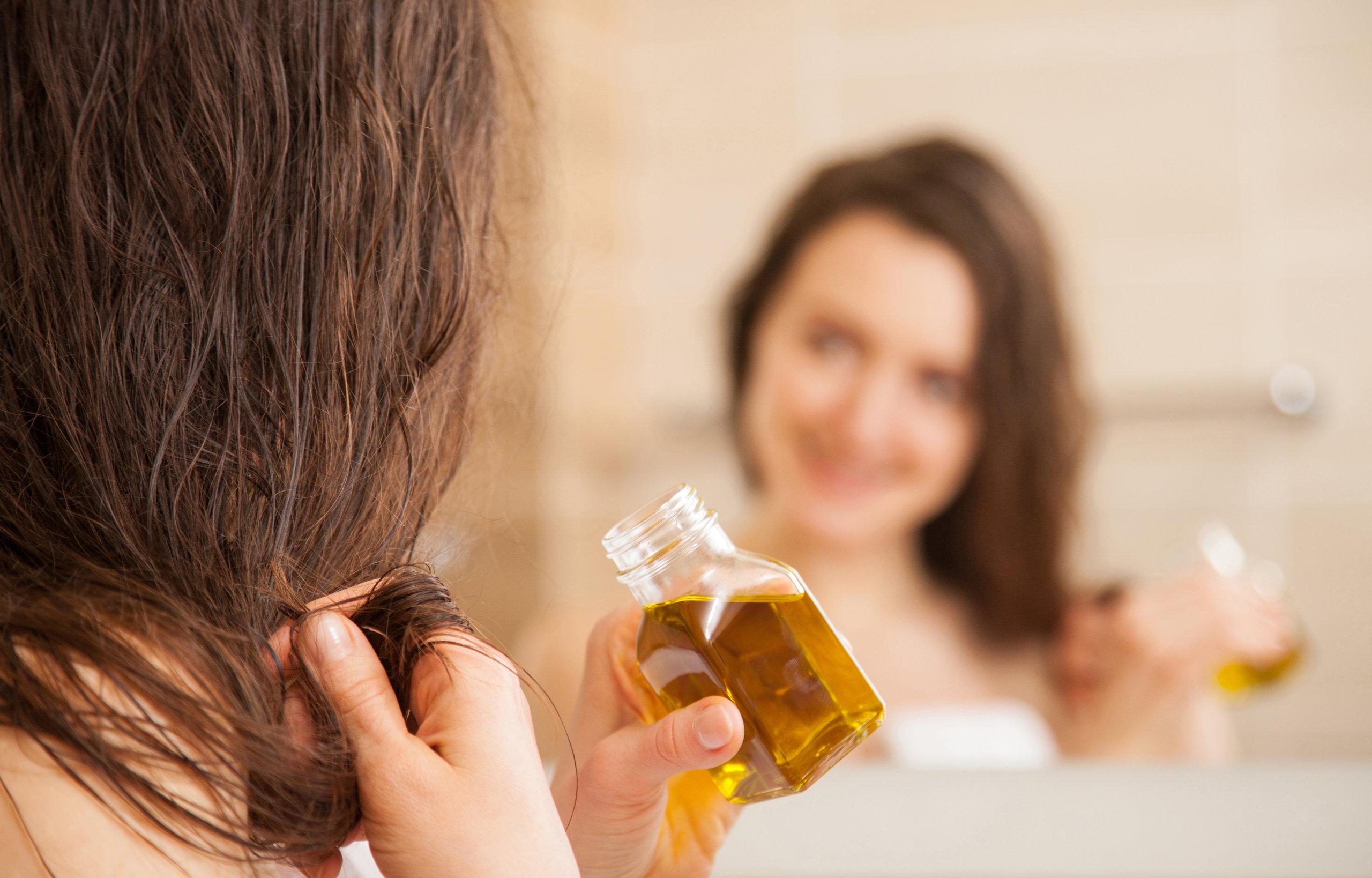 mujer joven de aplicar la máscara de aceite para las puntas del cabello en frente de un espejo sonriendo