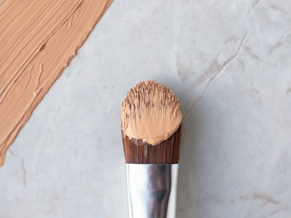 Makeup brush and creamy foundation on luxury marble background, above. Professional cosmetic cover, close-up