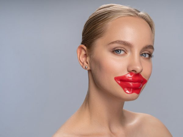Modern cosmetics. Kind blonde putting patch on lips while standing isolated on white