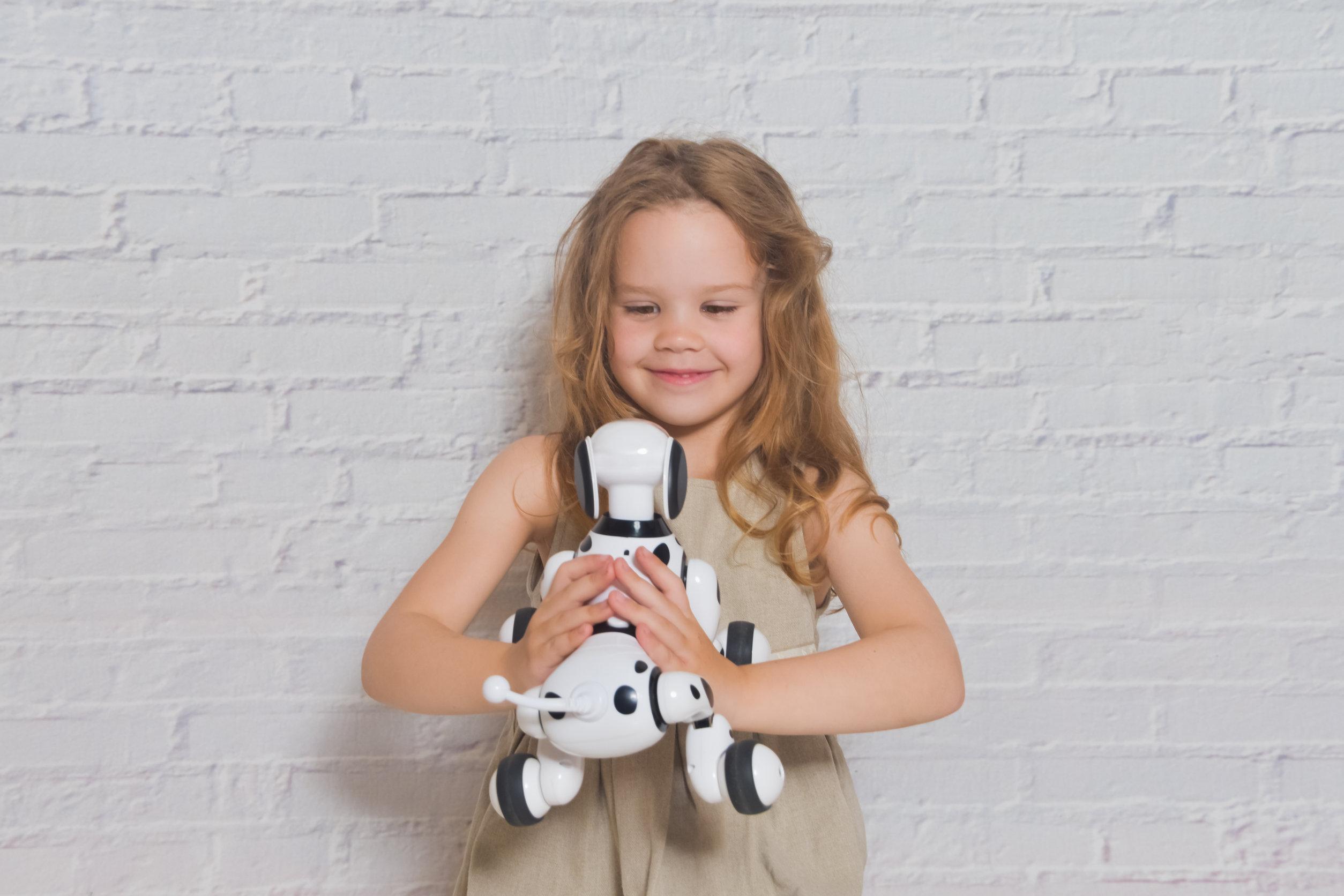 Niña jugando se encarga del perro robot