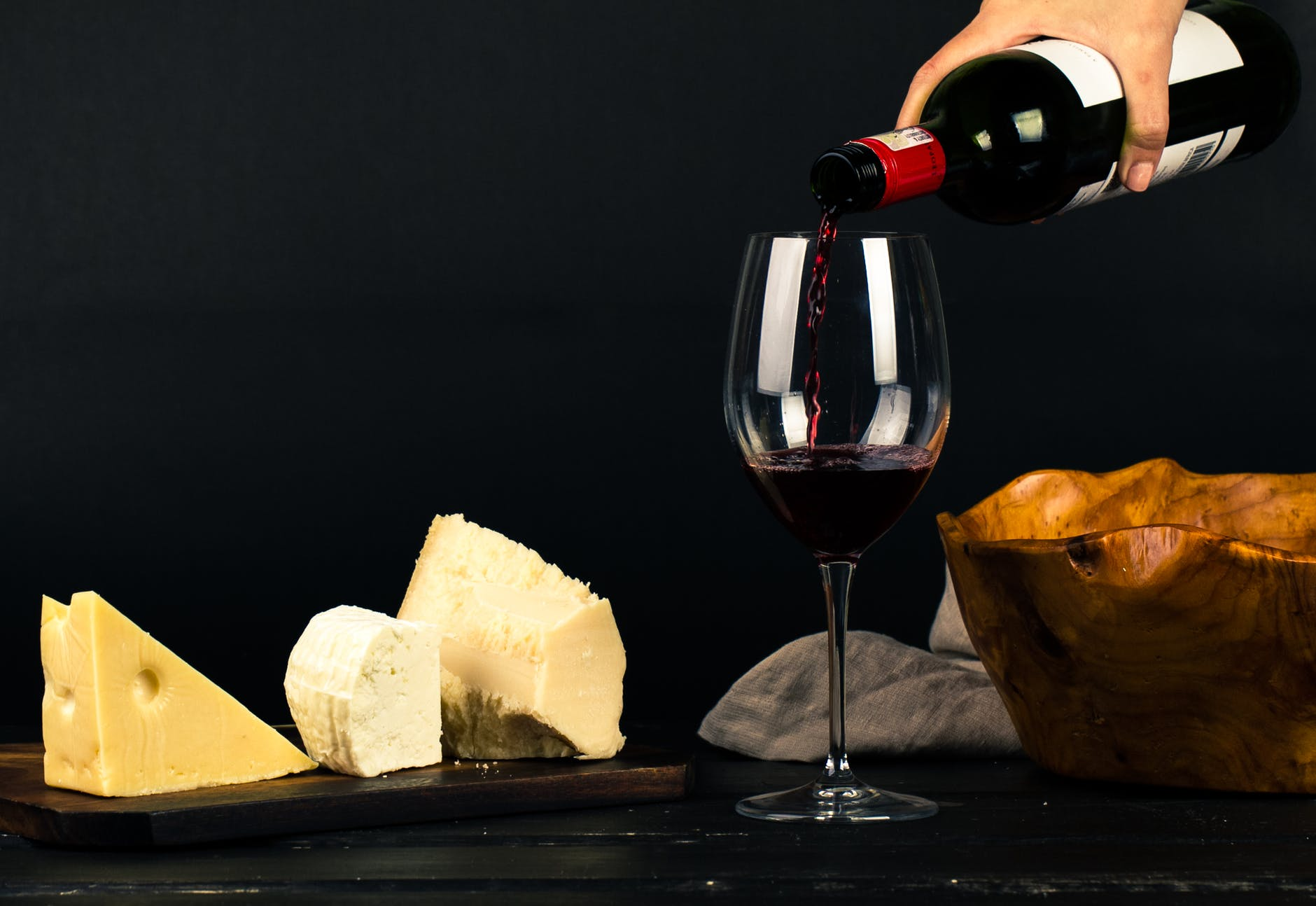 Copa de vino junto a quesos como aperitivo