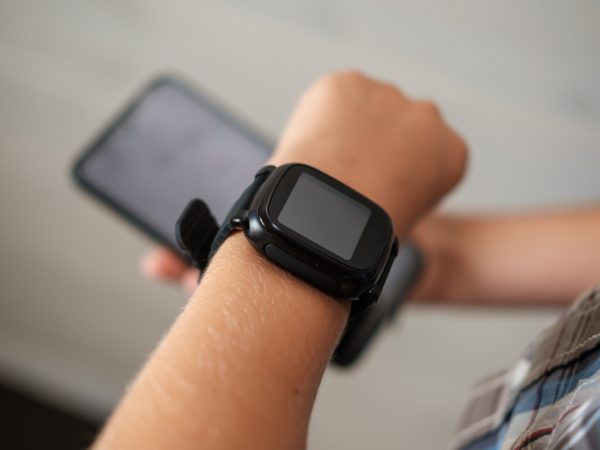 black smart watch on the boy's hand and black smartphone in the other hand