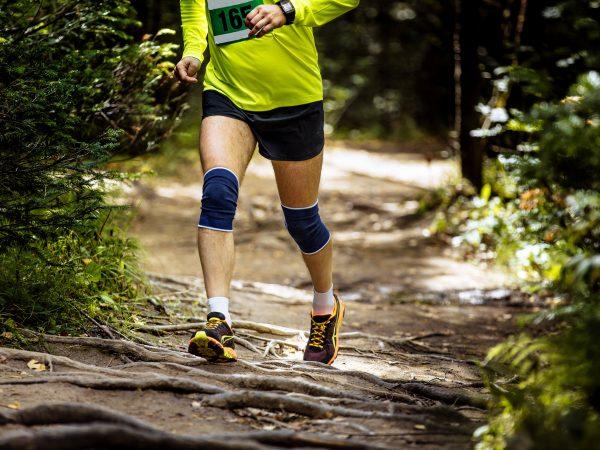 athlete marathon runner running in woods exposed roots of trees, knees in kneepads