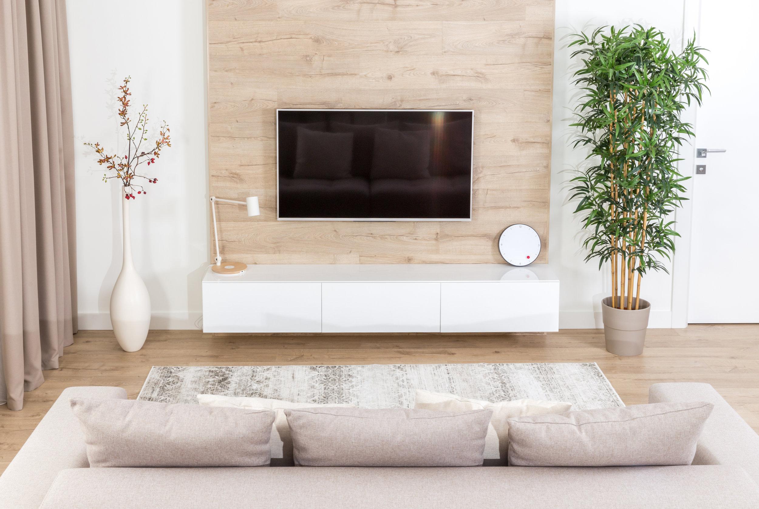 Sala de estar con sofá y tv led en una pared de madera en un interior moderno