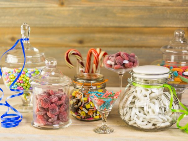 Multicolored candies in glass candy jars.
