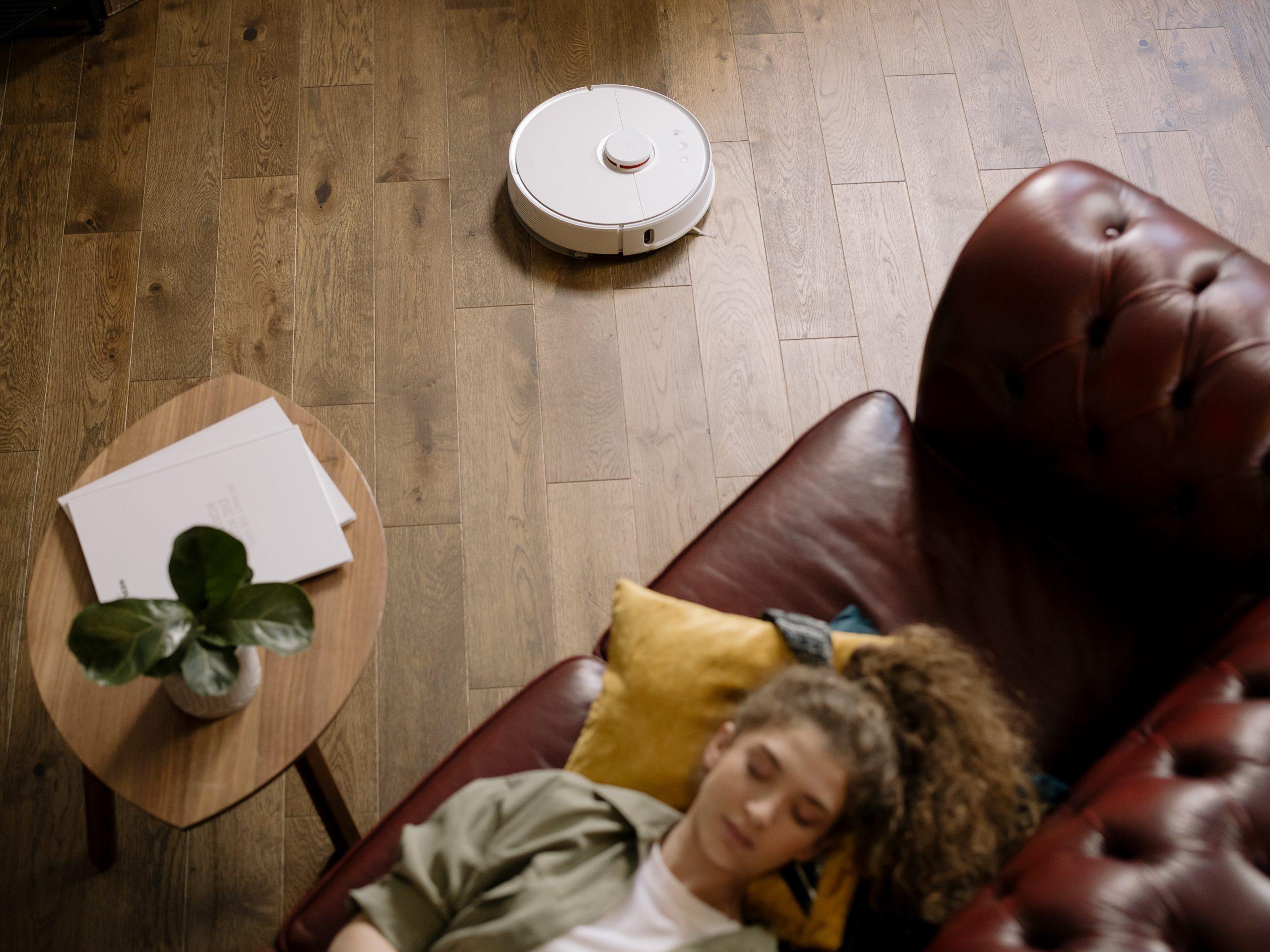 Mujer descansando mientras aspiradora realiza limpieza