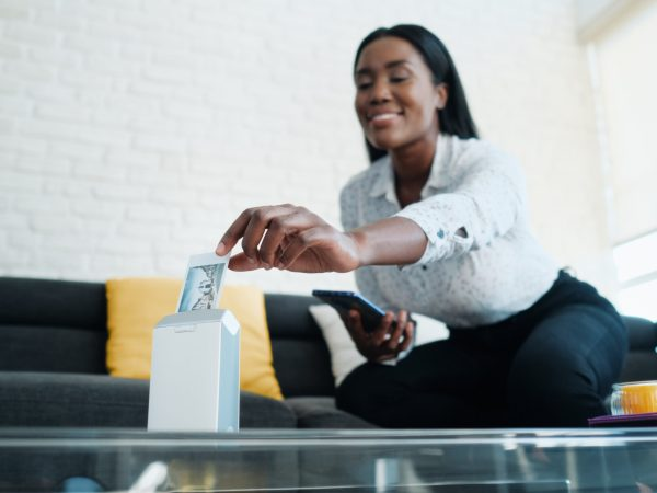 Black woman printing pictures with portable wireless mini printer at home. African american people sitting on sofa and archiving prints in photo album