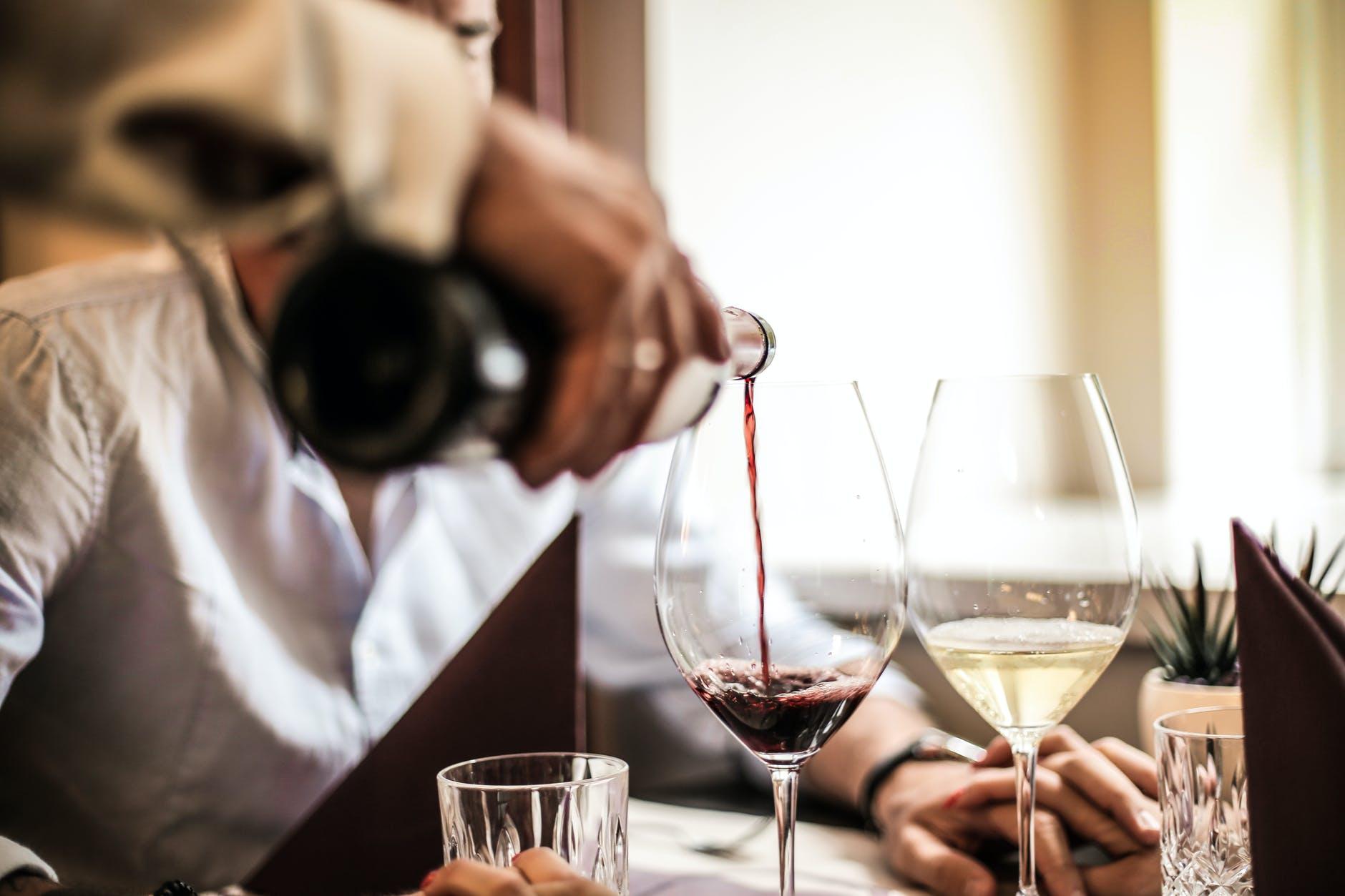 Mesero sirviendo vino en copas