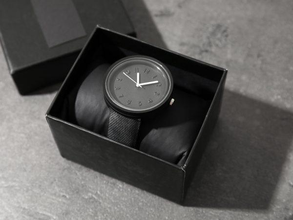 Box with stylish wrist watch on gray table. Fashion accessory