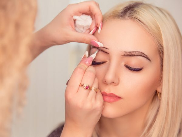 Changing the shape of the brows. Stylist drawing the eyebrows with dark pencil. Micropigmentation work flow in a beauty salon. Woman having her eye brows tinted with Semi-permanent makeup, eyes closed