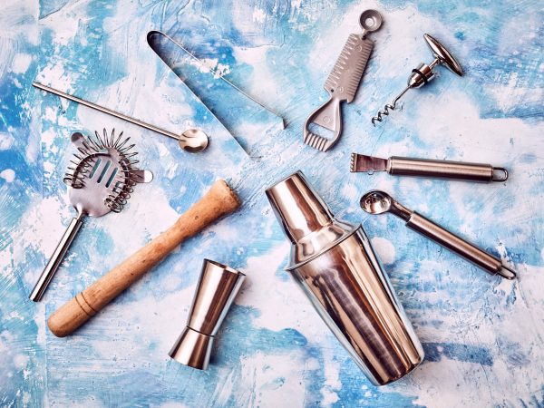 Set of Cocktail Bar utensils arranged in circle against abstract blue background
