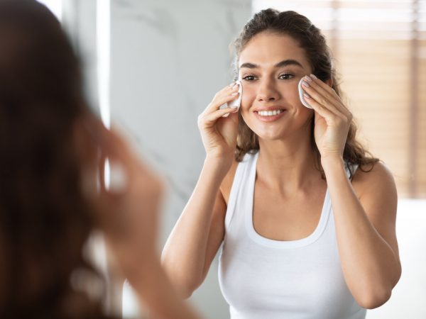 Facial Skincare. Young Lady Using Cotton Pads Cleaning And Moisturizing Skin, Removing Makeup Standing In Bathroom, Looking In Mirror Indoors. Selective Focus