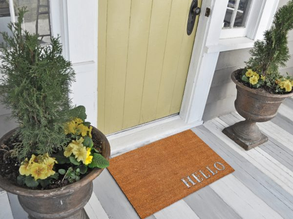 """Classic beige and Silver zute / coir Outdoor Door mat with """"Hello"""" text outside home with yellow flower pots"""