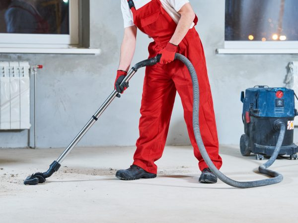 worker cleaning and removing construction dust with vacuum cleaner after repair