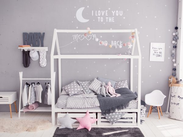 A cot-house, a rocking horse, children's clothes, a shelf with letters. On the bed is a plaid with cushions and toy hares. Interior in gray tones