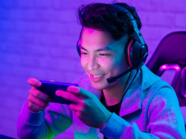 Young Asian Handsome vlogger having live stream and play online Video Game