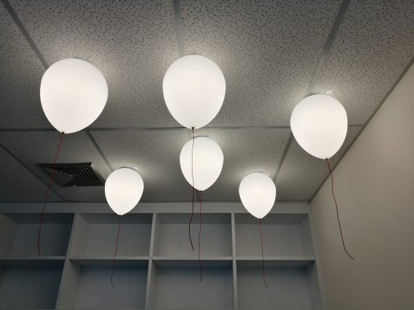 LED white creamy balloons burning fly away in the sky at night in the office room with blur white wood shelf background, holiday celebration decoration