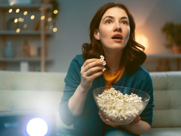 Young woman watching projector, TV, movies with popcorn in the evening. Girl spending time at home.