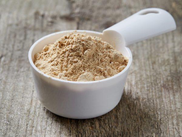 Measuring scoop of maca powder on wooden table