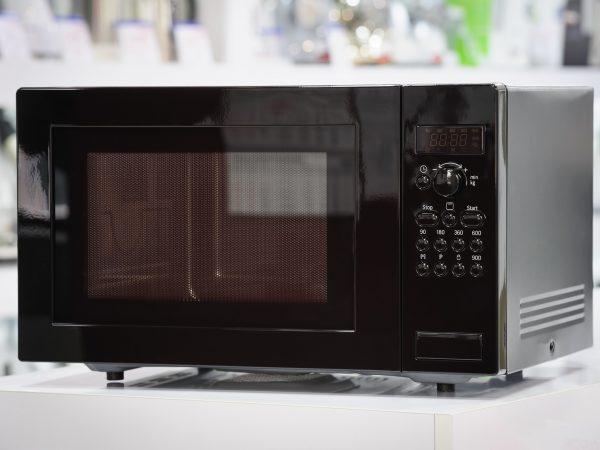 single black microwave oven at retail store shelf, defocused background