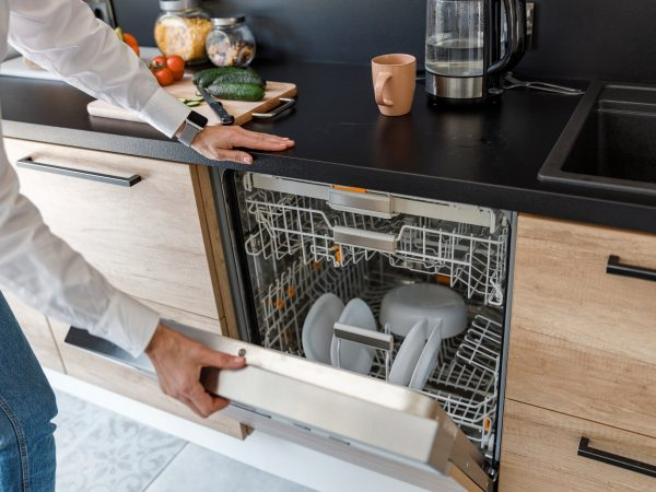 lady opening the door of the dishwasher stock photo
