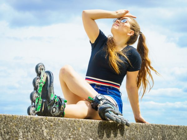 Young woman wearing roller skates outdoor. Fashionable fit girl having fun resting at sunny summer day.