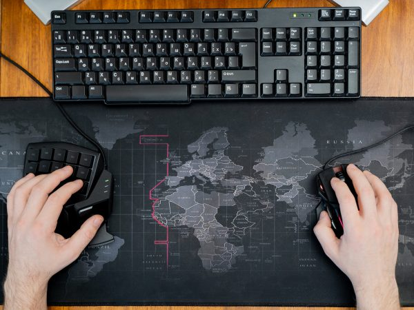 one hand on the gaming keyboard, the second on a computer mouse on a background of a computer mat with a world map