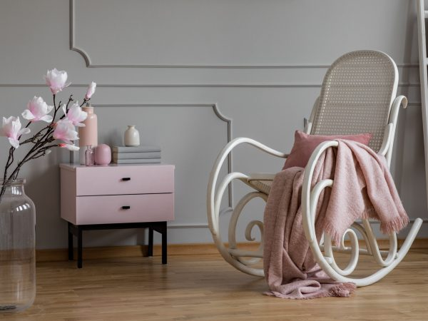 Flowers and rocking chair with blanket in grey and pink living room interior with cabinet. Real photo