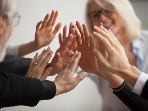 Hands of diverse business people giving high five, smiling team members, teachers and students promising help unity in goal achievement, coaching support in mentoring teamwork concept, close up view
