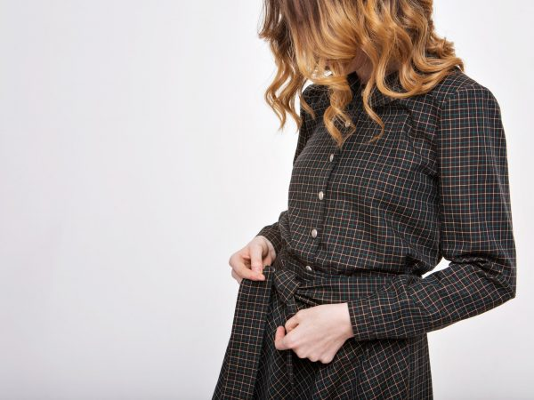 girl ties a belt on a dress. Hands on fabric background close-up. Element of clothes
