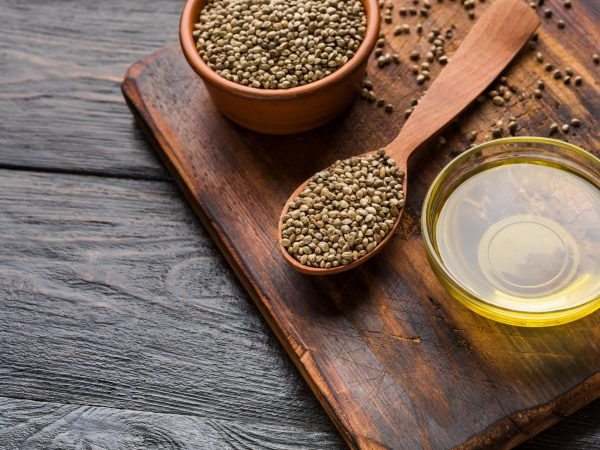 Hemp oil and hemp seeds in bowls on board over wooden background, copy space. Natural medicine concept