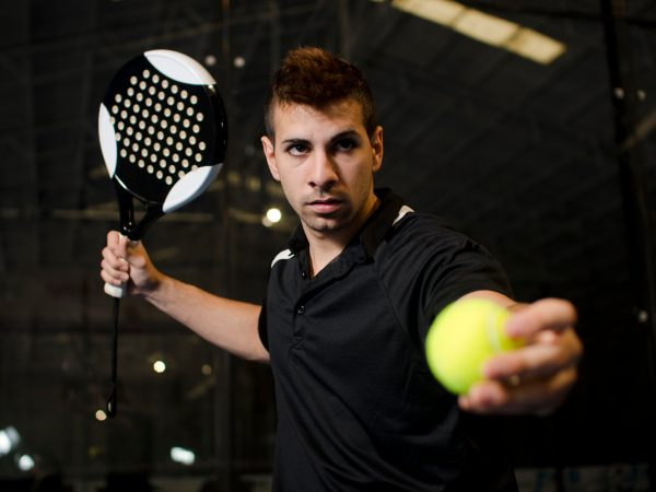Paddle tennis player in court ready for serve.