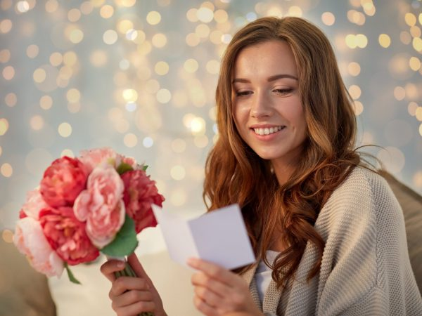 holidays, winter, birthday and people concept – happy young woman with flowers reading greeting card in bed at home bedroom