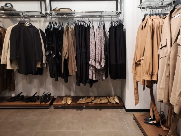 Closeup of black and gray clothes hanging on clothing rack showed for selling at shop. Row of clothes garment spring, autumn and winter woman fashion collection