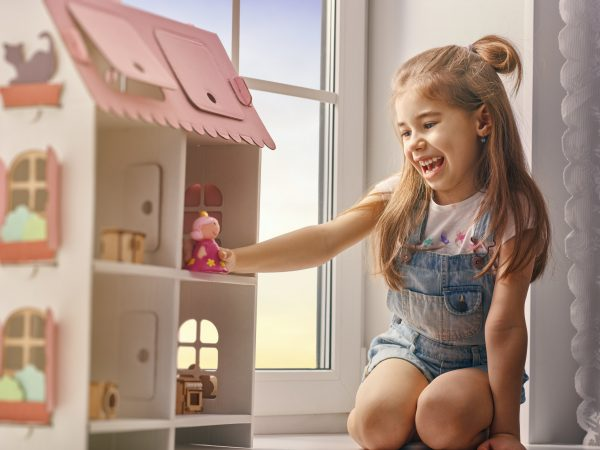 Happy girl plays with doll house and teddy bear at home. Funny lovely child is having fun in kids room.