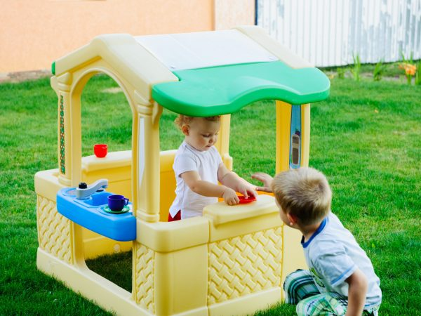 Children playing in toy house at playground