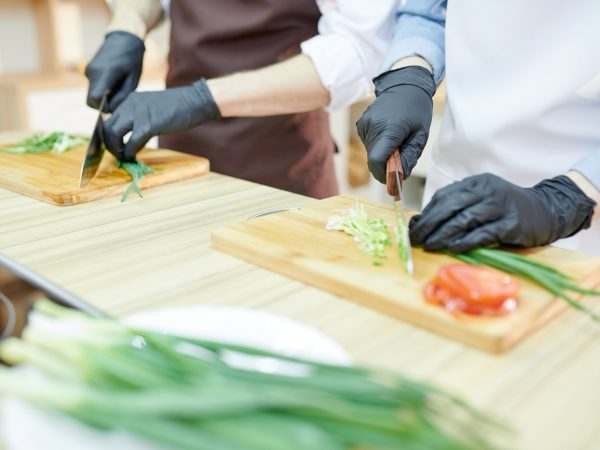 Closeup of unrecognizable female chef cutting vegetables standing at wooden table in restaurant kitchen with assistant, copy space