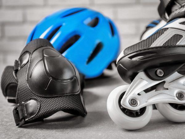 Roller skate and knee pad on floor, closeup